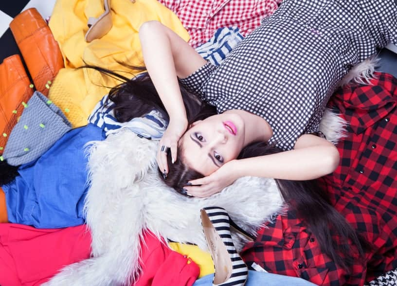 Young woman laying in a pile of clothing and shoes