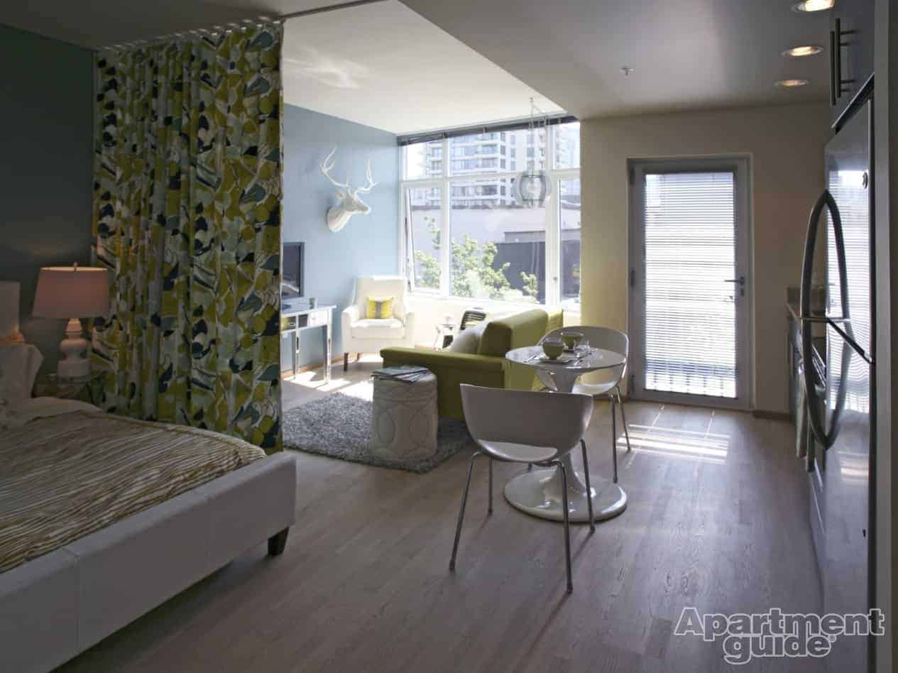 This studio apartment features a brightly colored curtain that separates  the bedroom area from the rest