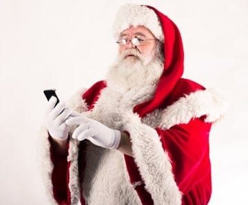 "Santa Claus, perusing the ""naughty or nice"" app on his cell phone -- indispensable!"