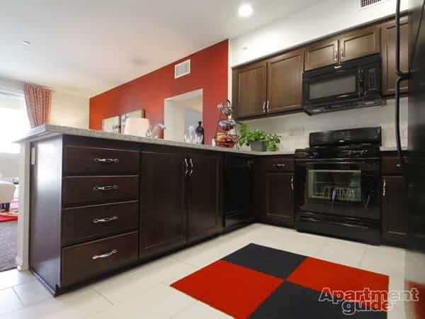 Red and black accents bring kitchen and living areas together at Main Street Village in Irvine, California