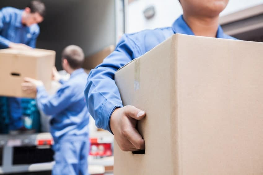 Man holding box outside of moving truck