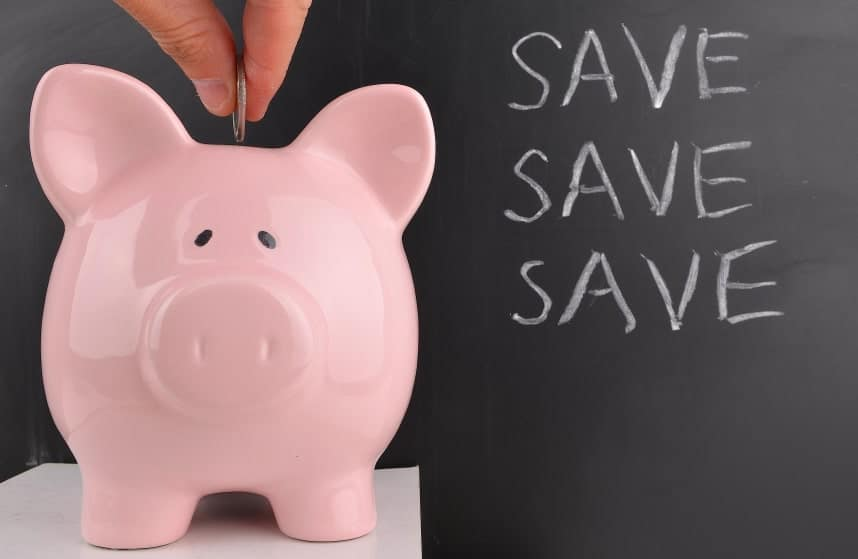 Putting a coin in a pink piggy bank to save