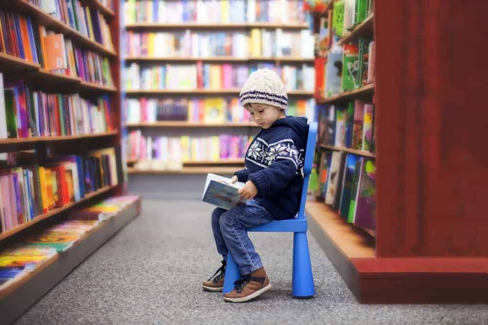 kid reading a book at the library