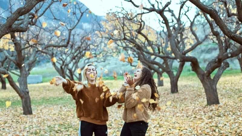 girls outside with fall leaves