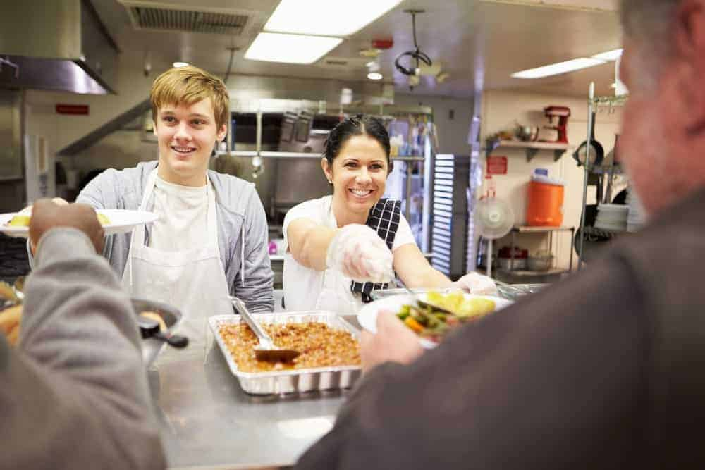 family volunteering at food kitchen