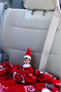 Elf in a car with a blanket