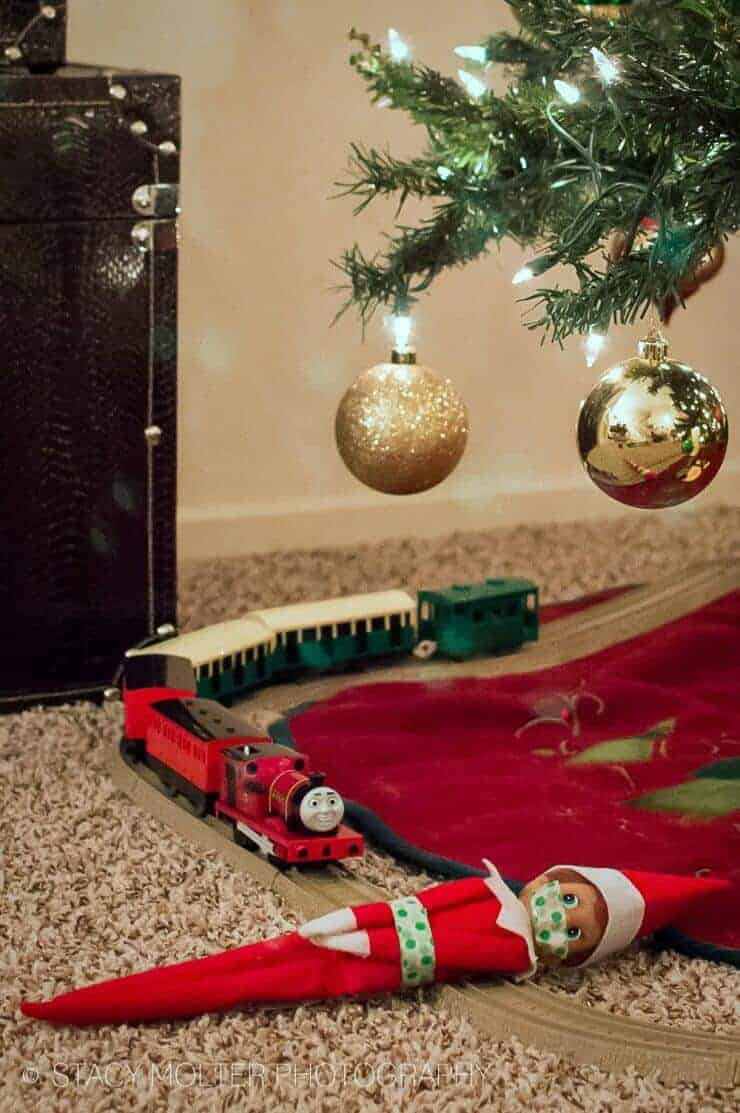 Elf laying on toy train tracks
