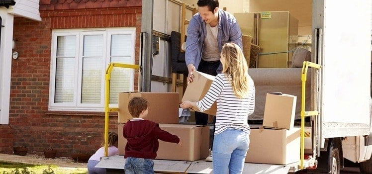 family unpacking moving van