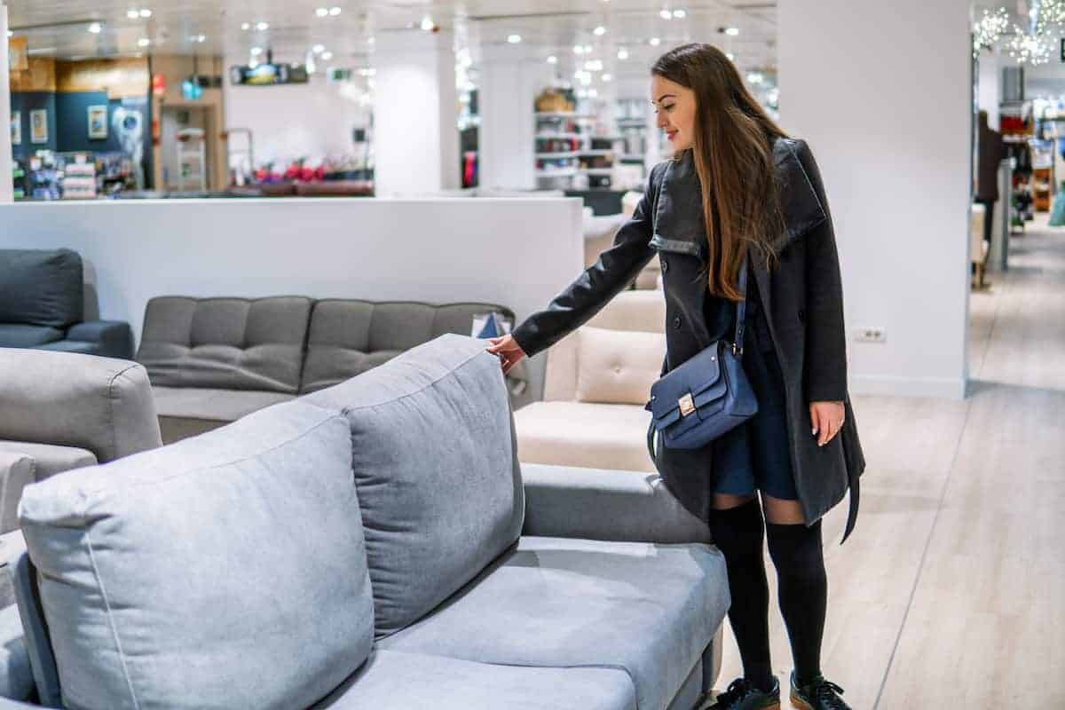 woman looking at couch in a store