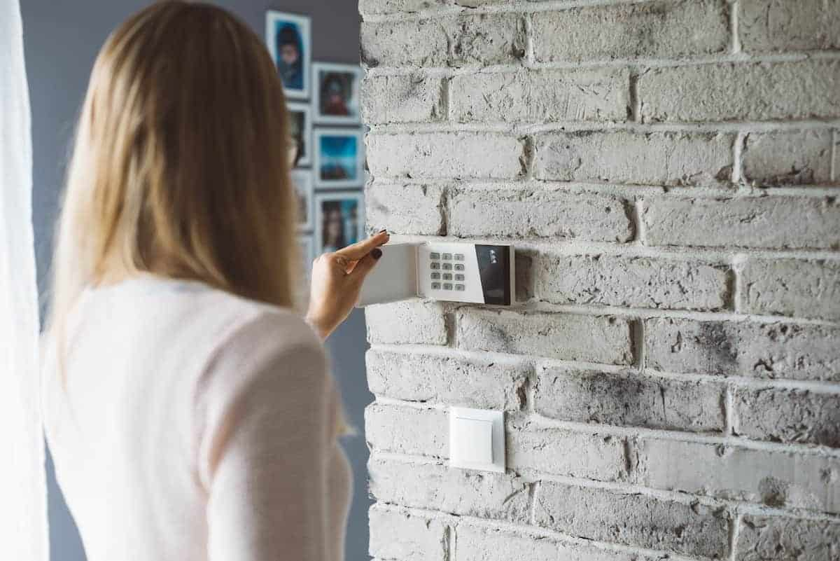 Woman entering her code on an alarm system keypad stuck to the wall