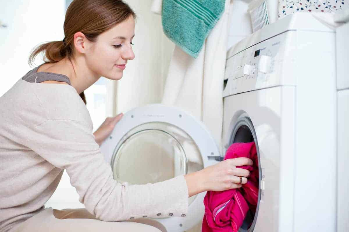 Young woman putting laundry into her washing machine