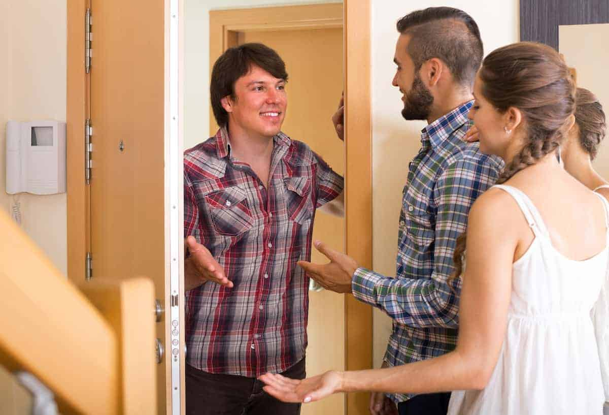 Male neighbor getting to know a young couple to help keep their apartment building safe