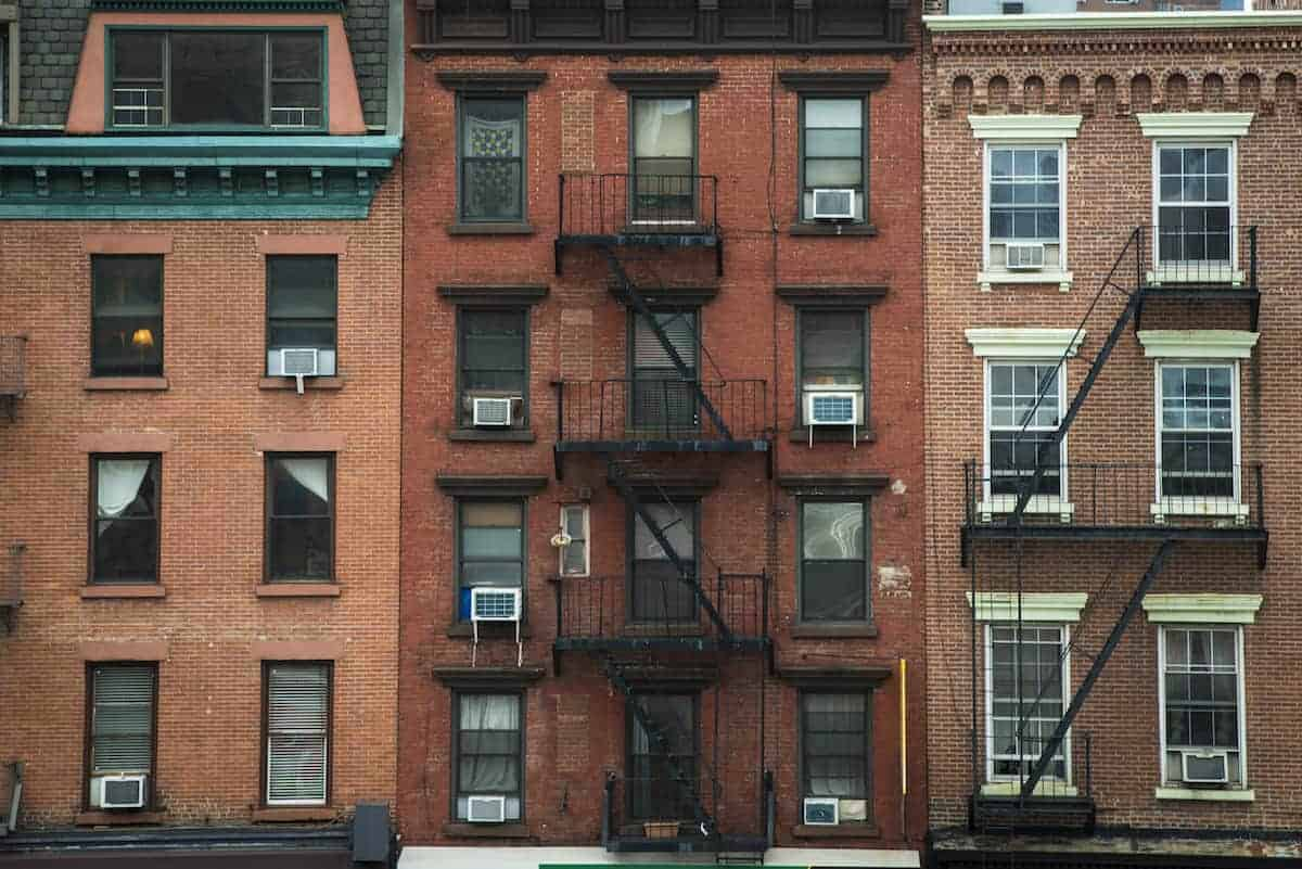 Three older apartment building with window AC units and fire escapes in New York City