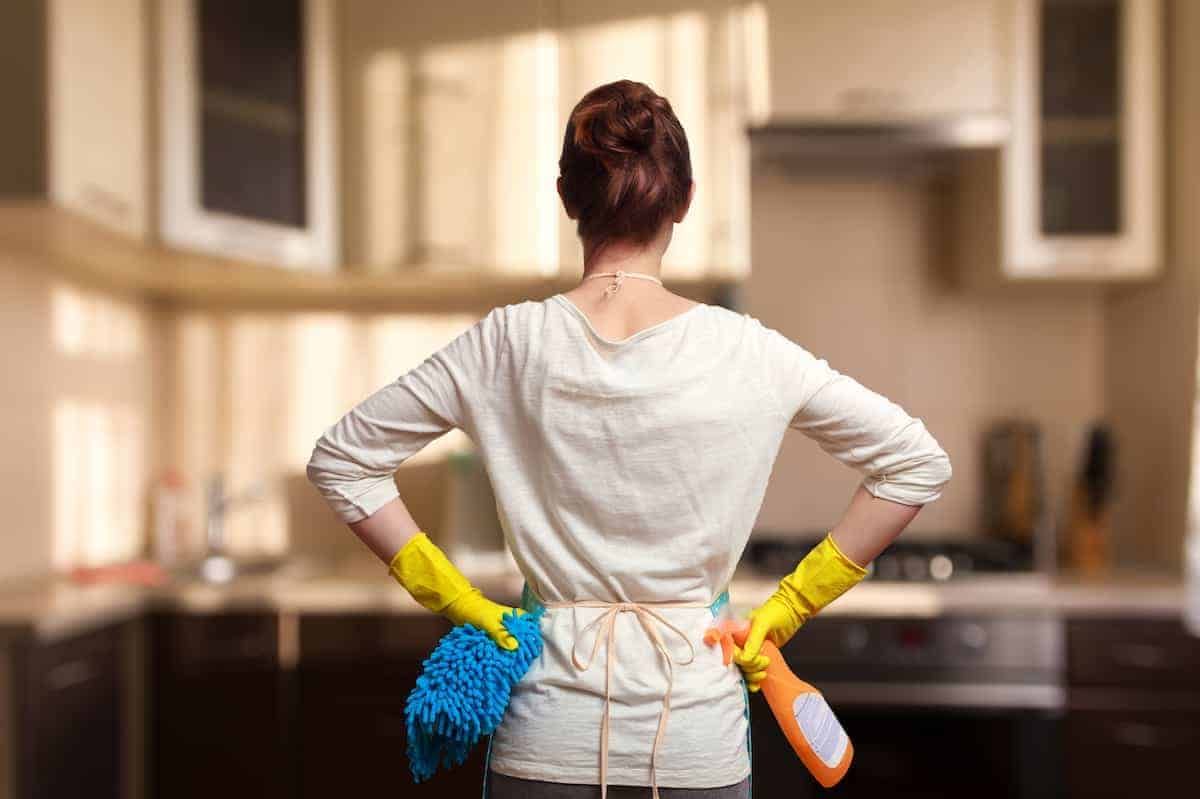 Woman looking at kitchen with cleaning supplies in hands