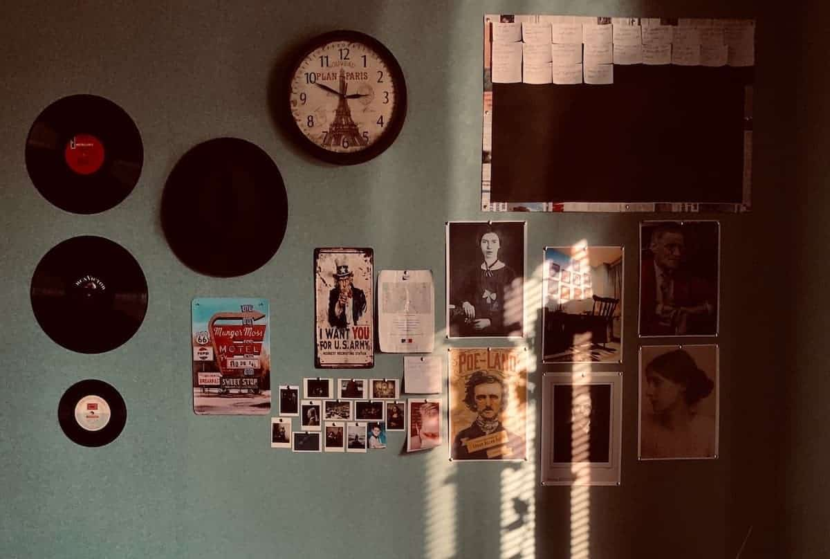 Wall with a variety of items hanging on the wall, from clocks to records to vintage posters