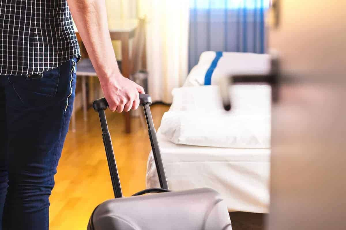 guy with suitcase entering bedroom