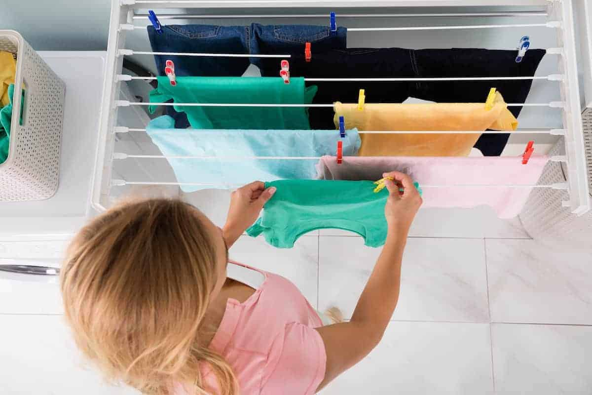 Woman using clips to hand wet clothing on a drying rack