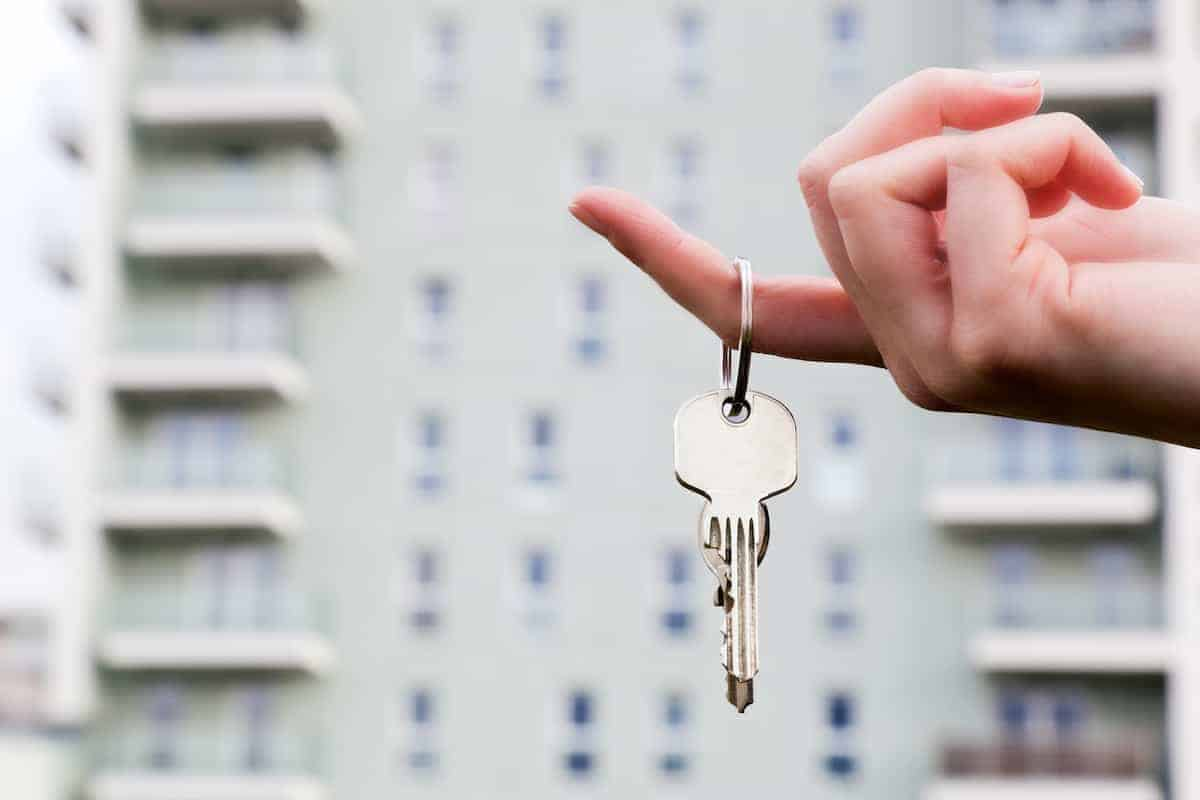 Hand dangling apartment keys by one finger in front of the building where the unit is located