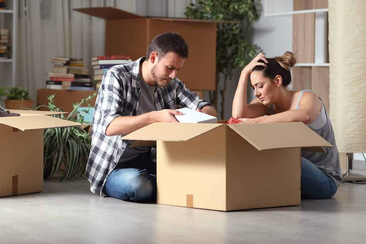 Stressed out couple packing to move out of their apartment