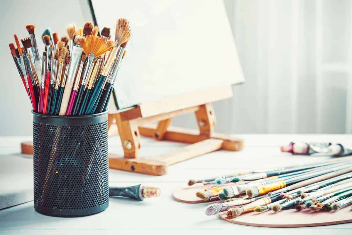 Art set up with blank canvas in an easel, assorted paint brushes and tubes of paint