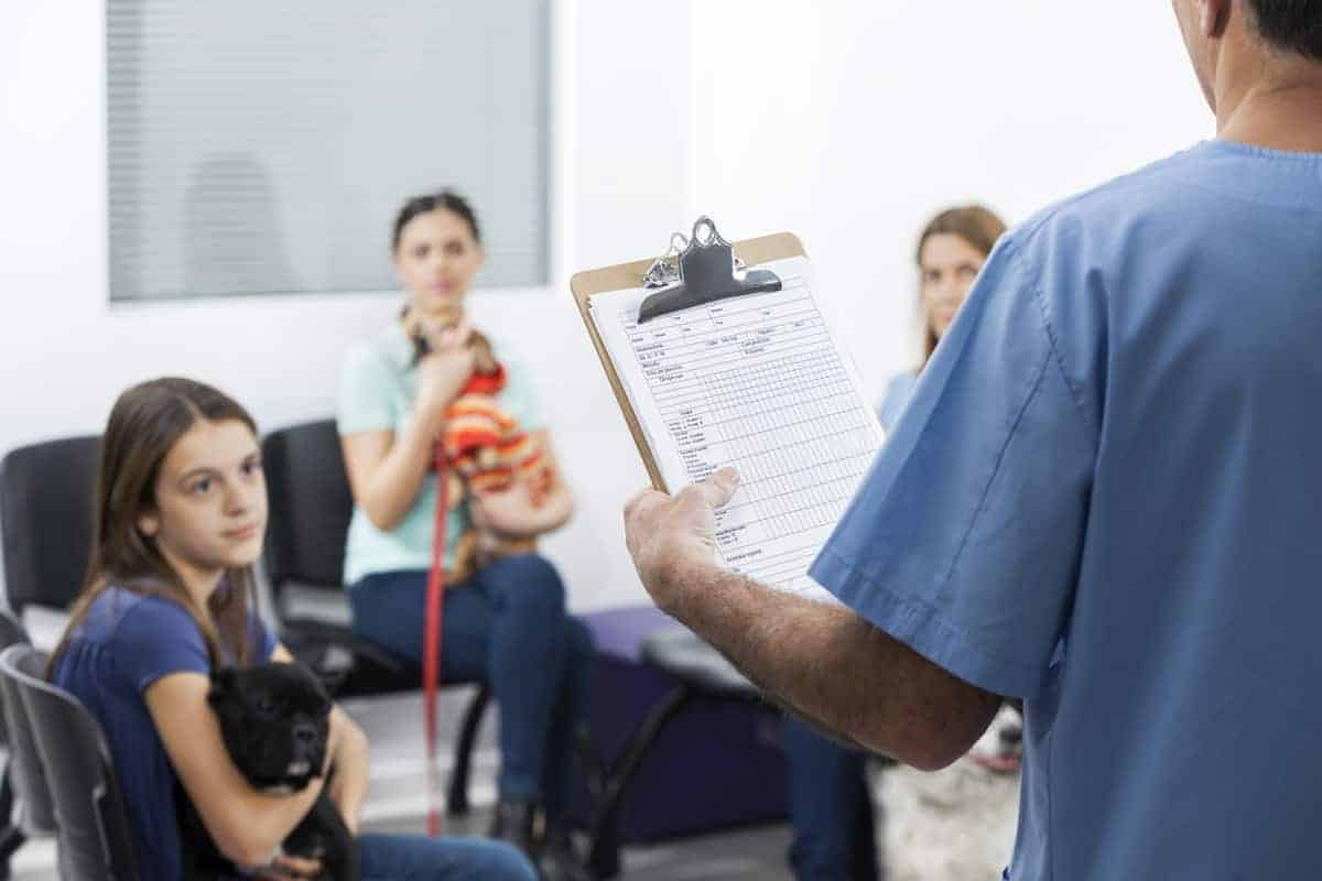 A few people sitting in a veterinary office waiting room while a nurse checks clipboard for who