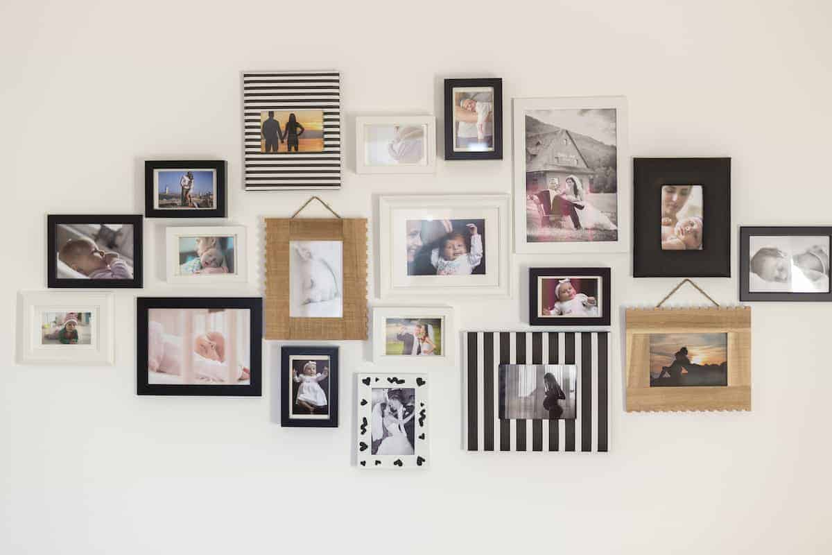 Wall of photographs in varying styles of hanging picture frames