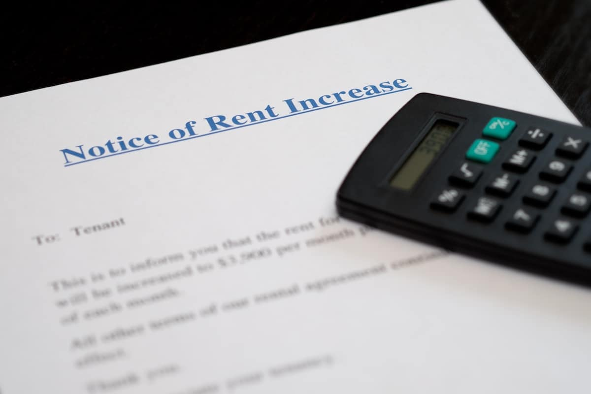 Formal notice of rent increase letter with calculator on top of the document
