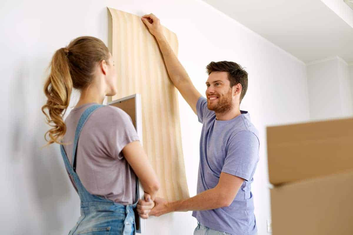 Young couple testing out yellow stripped temporary wallpaper in their apartment