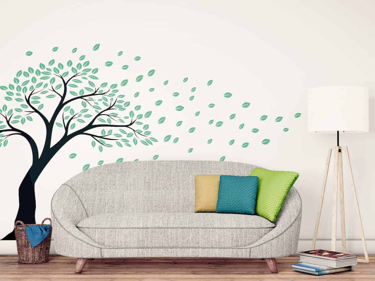 Living room couch with wall decal of a tree losing its leaves beside and behind it