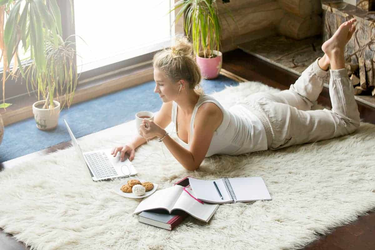 photo of woman in her college apartment on a laptop