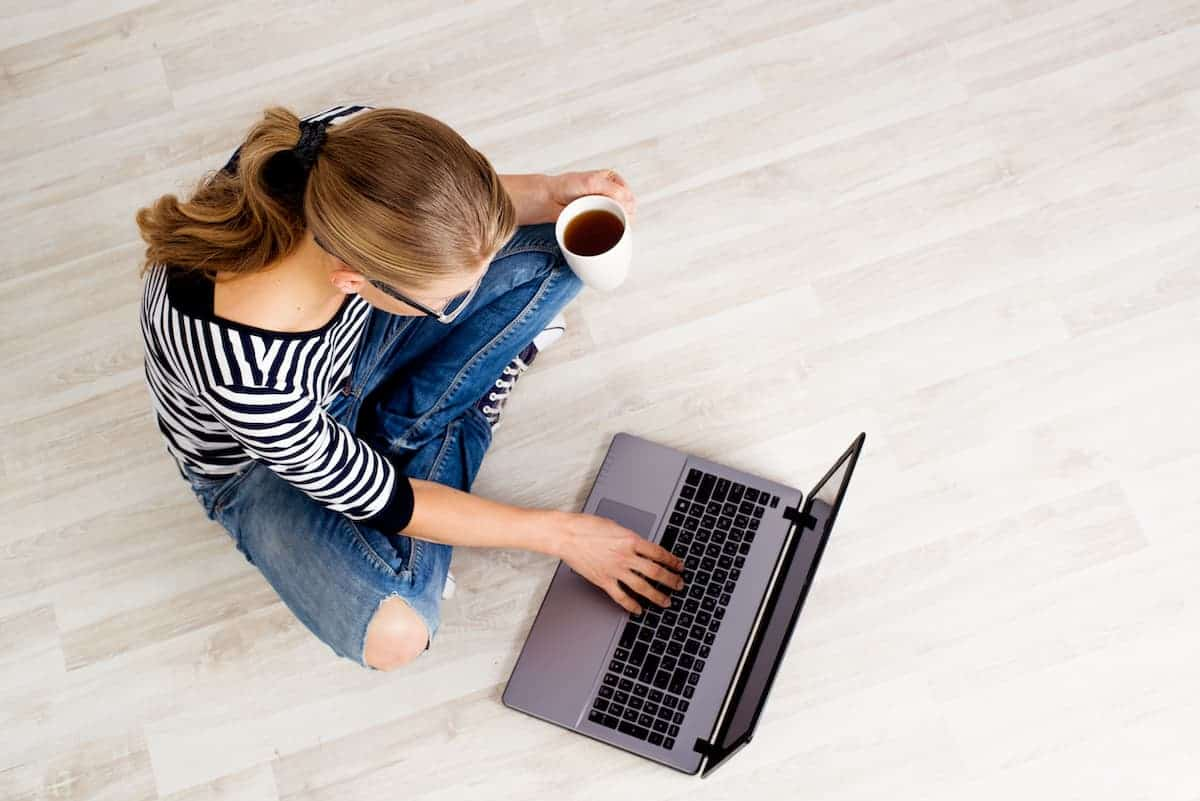Female sitting on floor with coffee and her laptop, searching available apartment listings