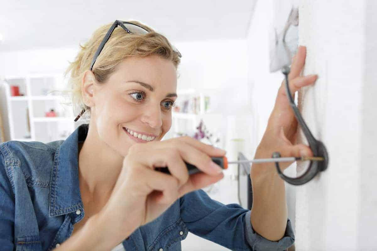 woman installing hooks on wall