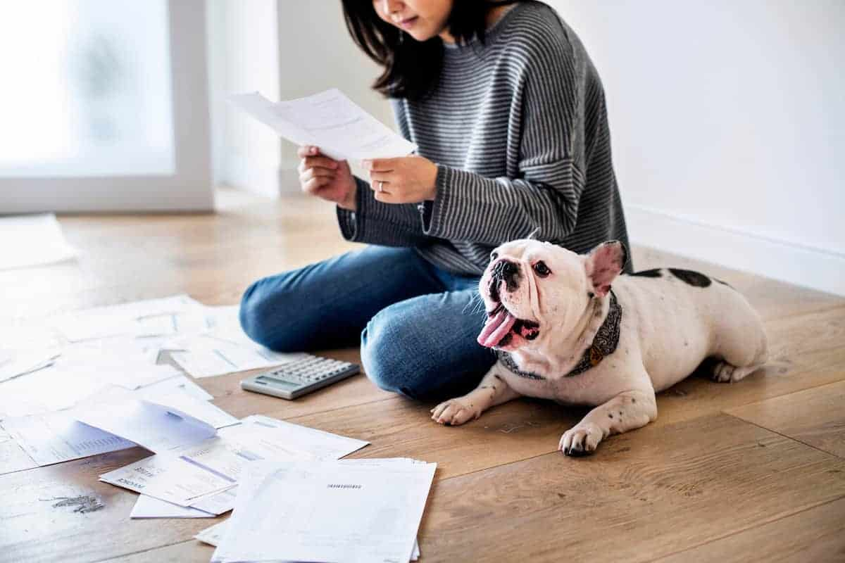 Woman sitting on floor with her bulldog reviewing a large pile of bills