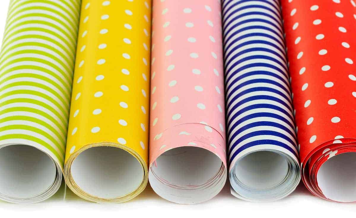 Rolls of wrapping paper in simple designs lined up in a row