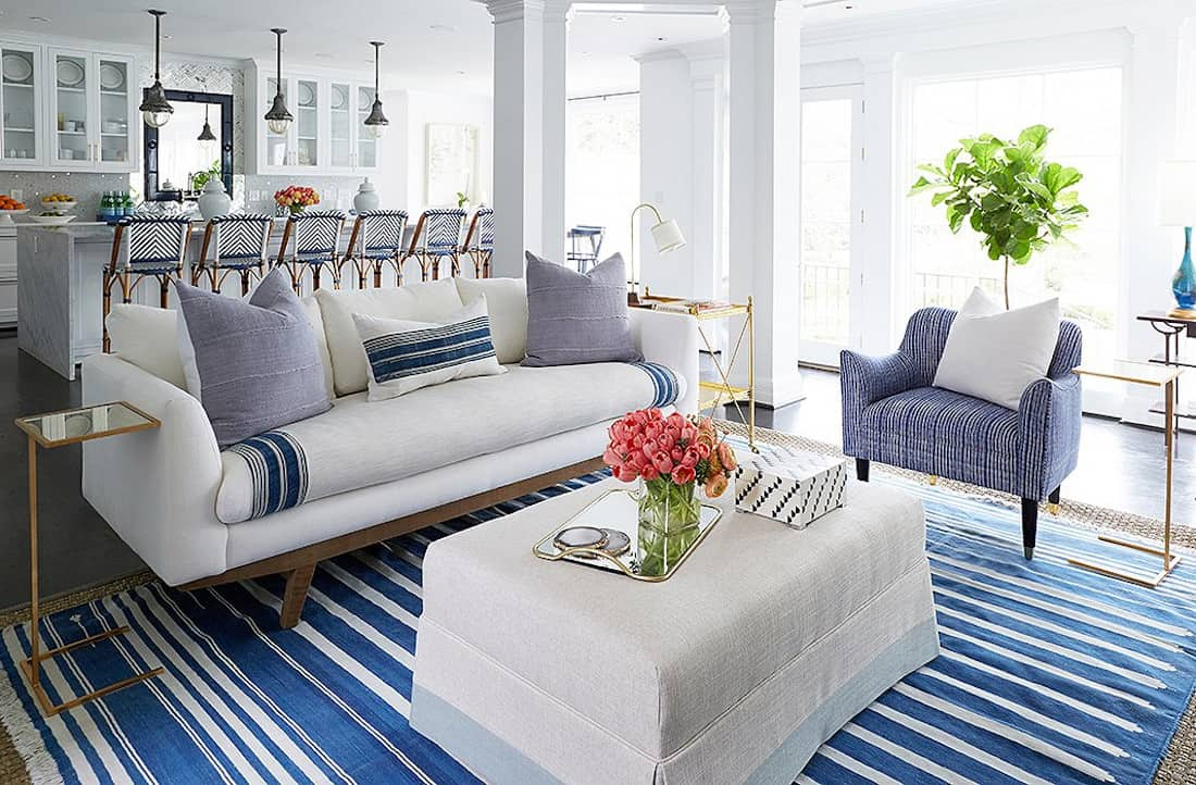 Roomy living room with white couches and a classic blue and white striped rug to tie the room together.