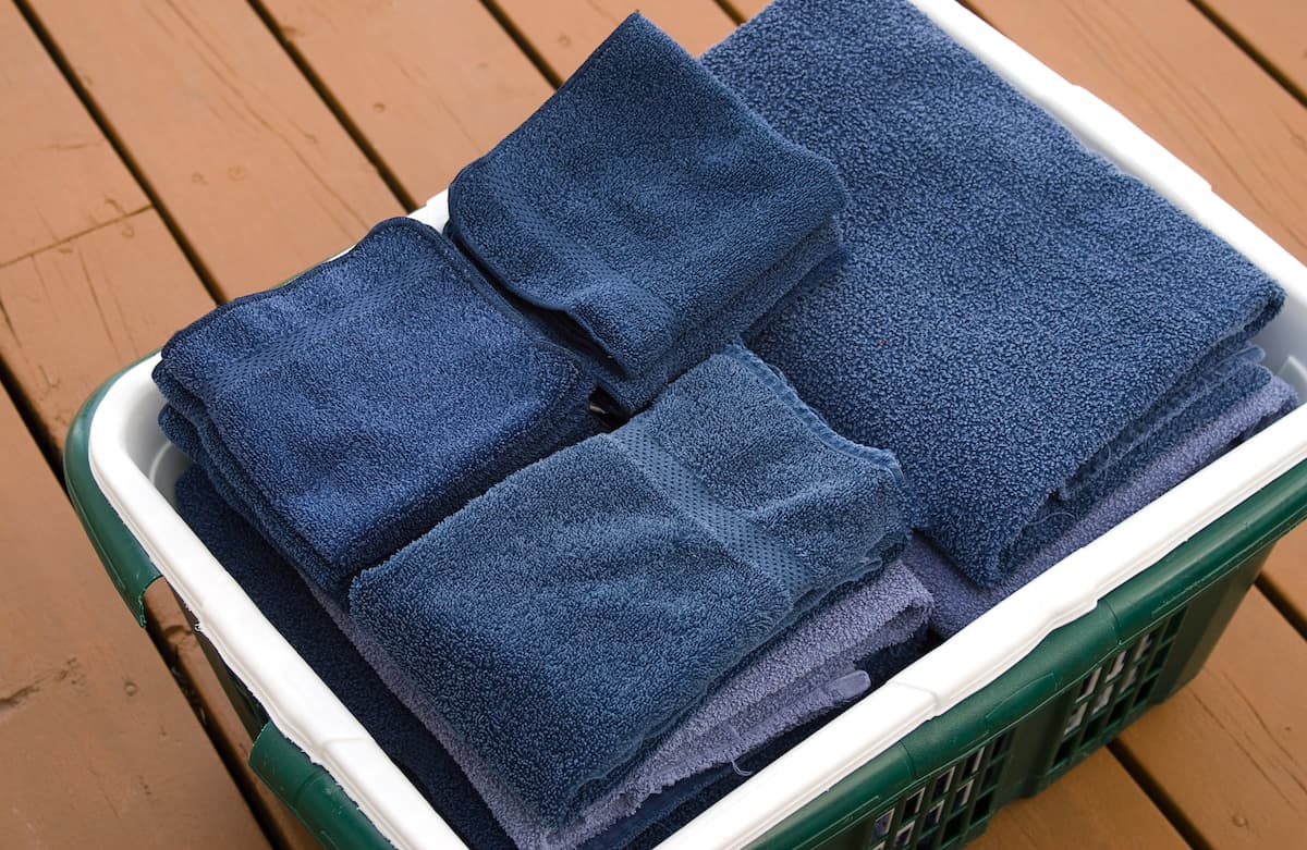 Laundry hamper full of clean, fluffy, blue towels, ready for use