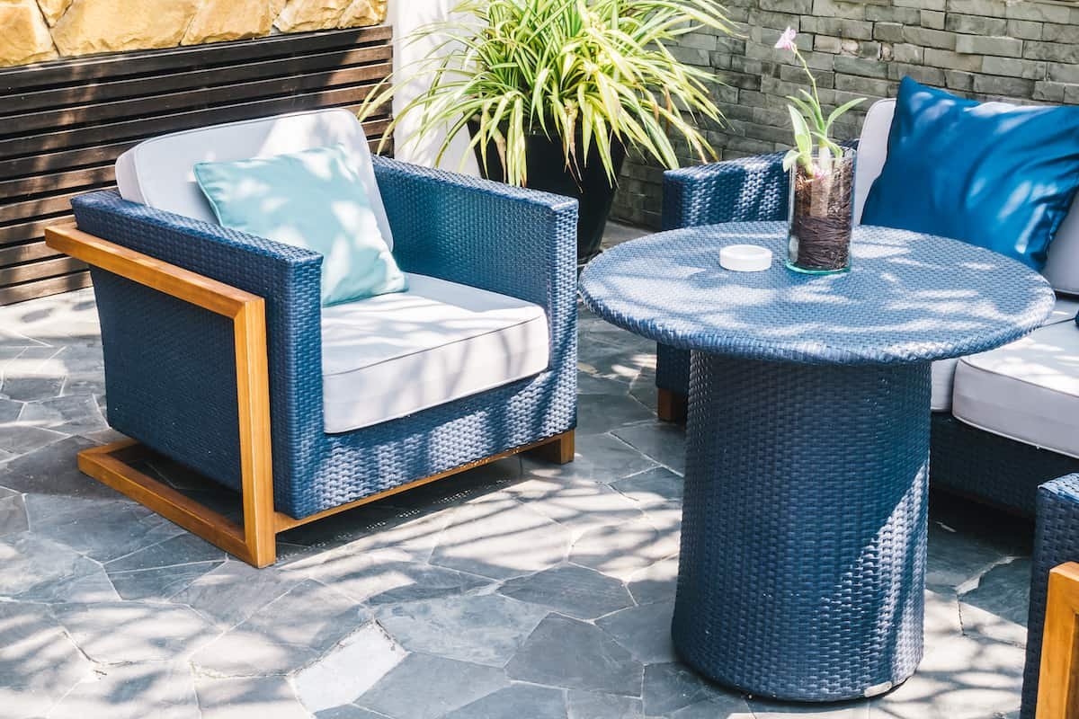 Collection of blue, wicker patio furniture with white cushions and lighter blue throw pillows