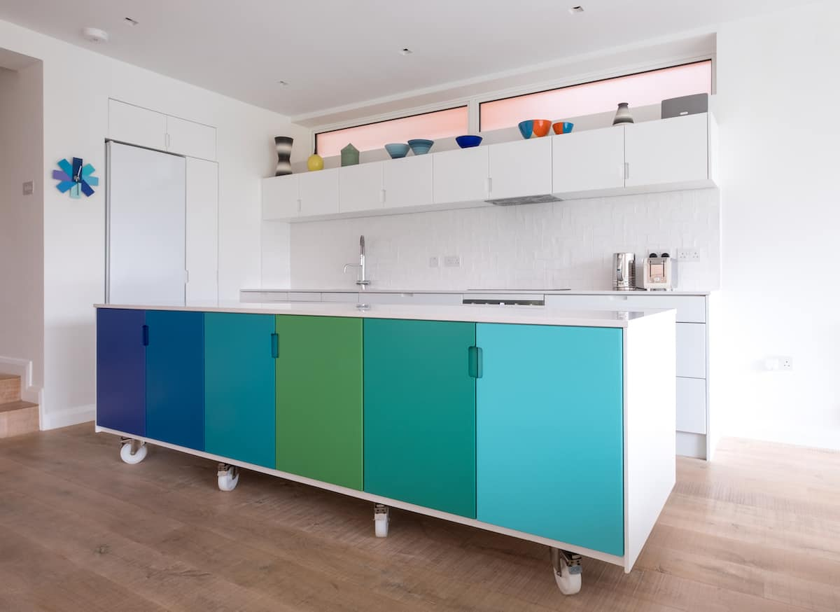 Kitchen cabinet with each door painted a different shade of blue or green for a colorful design