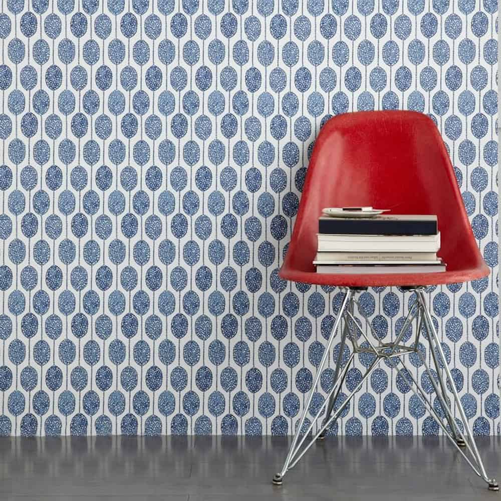 Modern red chair with a stack of books set in front of wall with a bold blue and white wallpaper.
