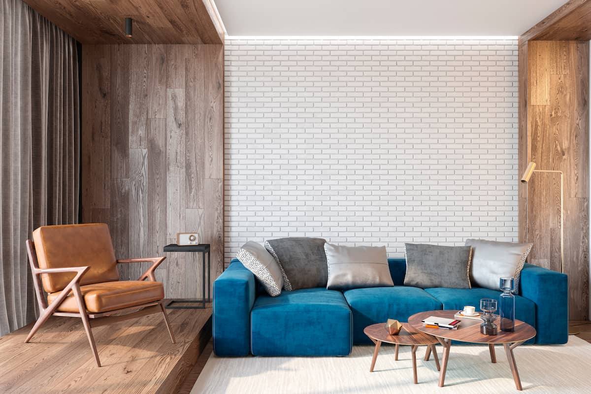 Blue, suede couch with gray throw pillows set against a whitewashed, brick wall in a living room that also has wood panels