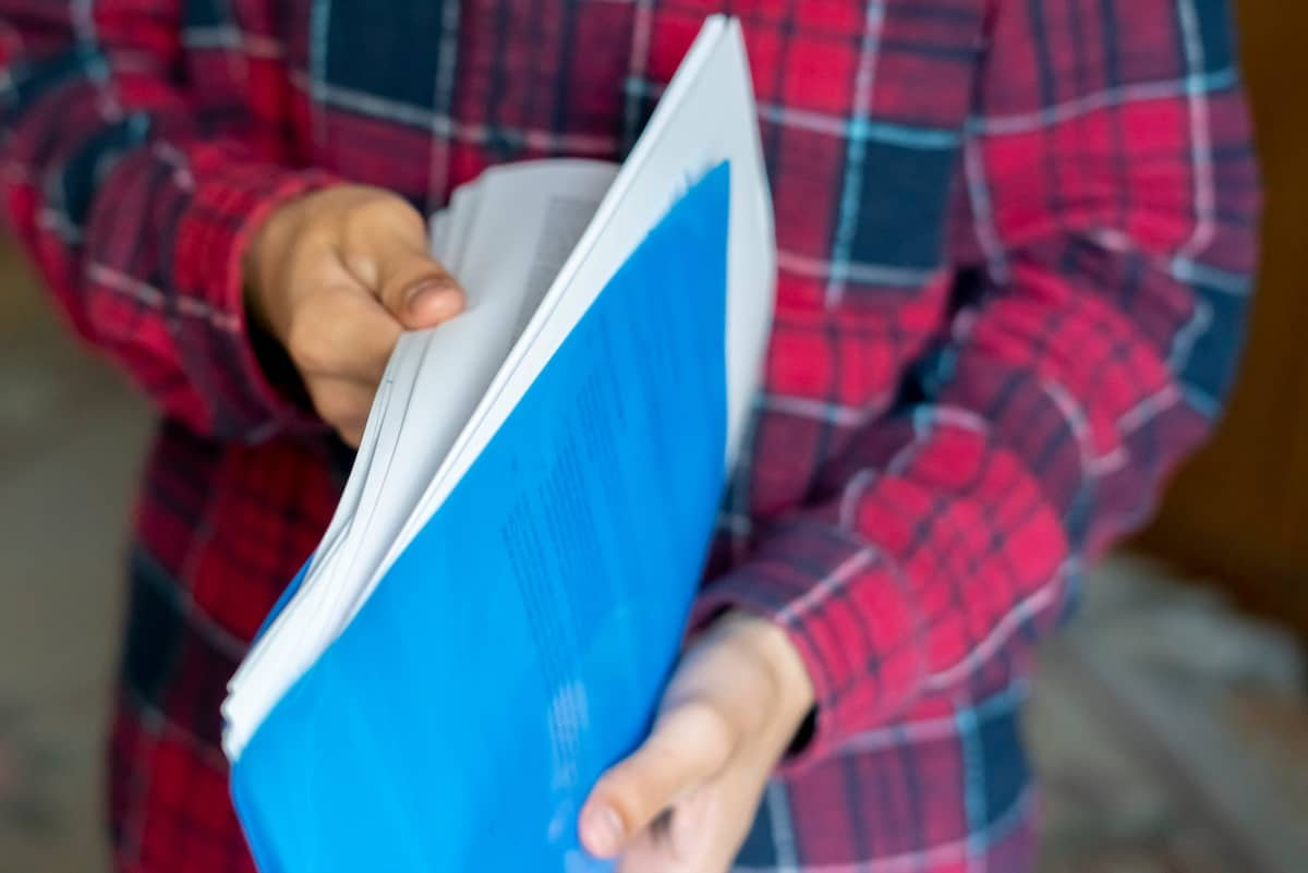 Close-up of hands thumbing through paperwork in a blue file folder, ready to sign a lease on an apartment