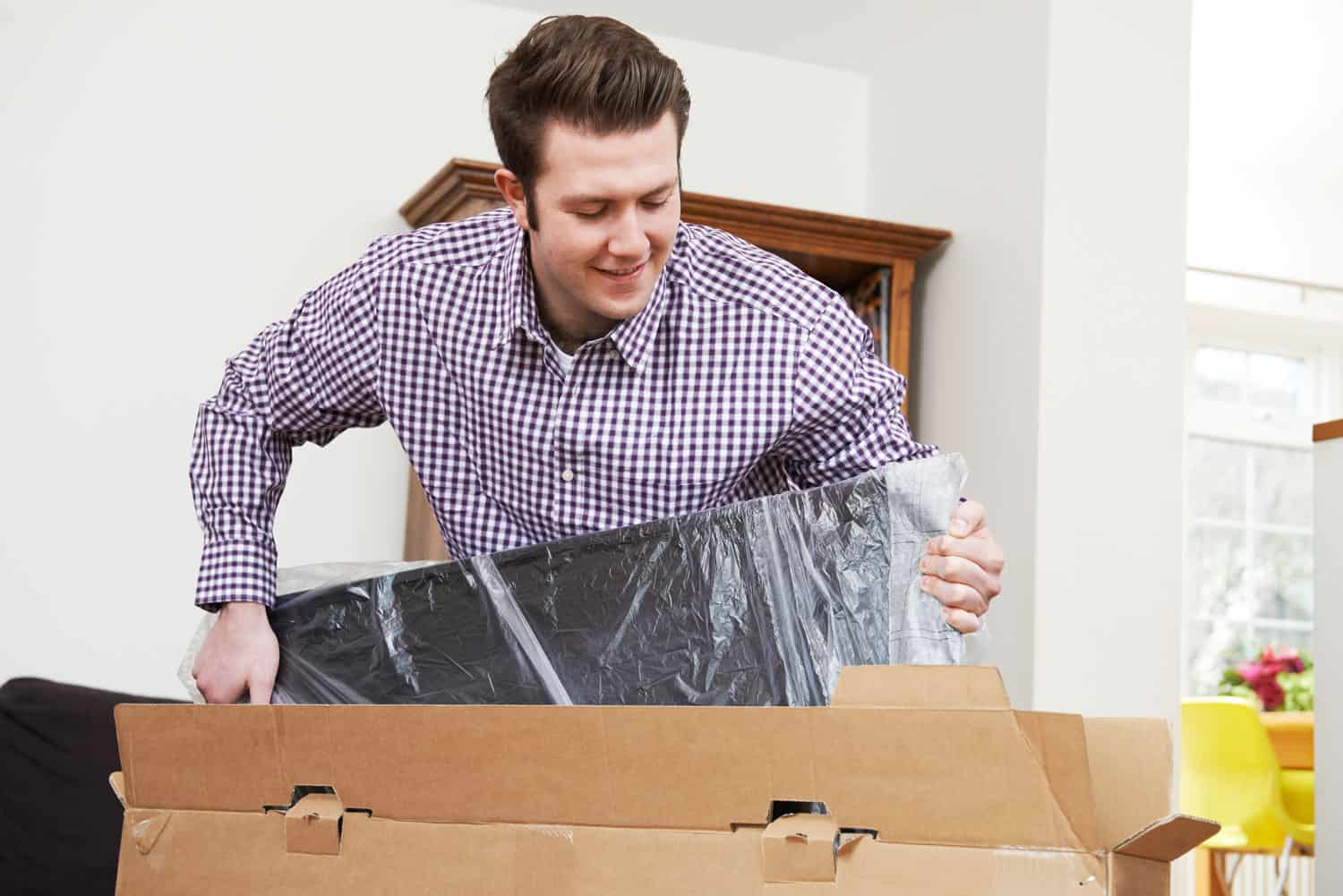 photo of man unpacking a TV