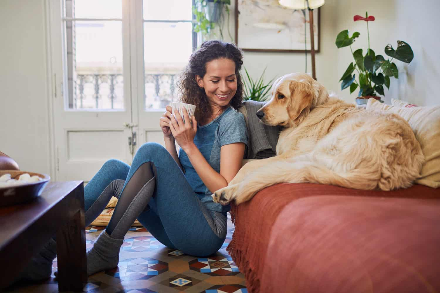 woman enjoying her apartment with her dog