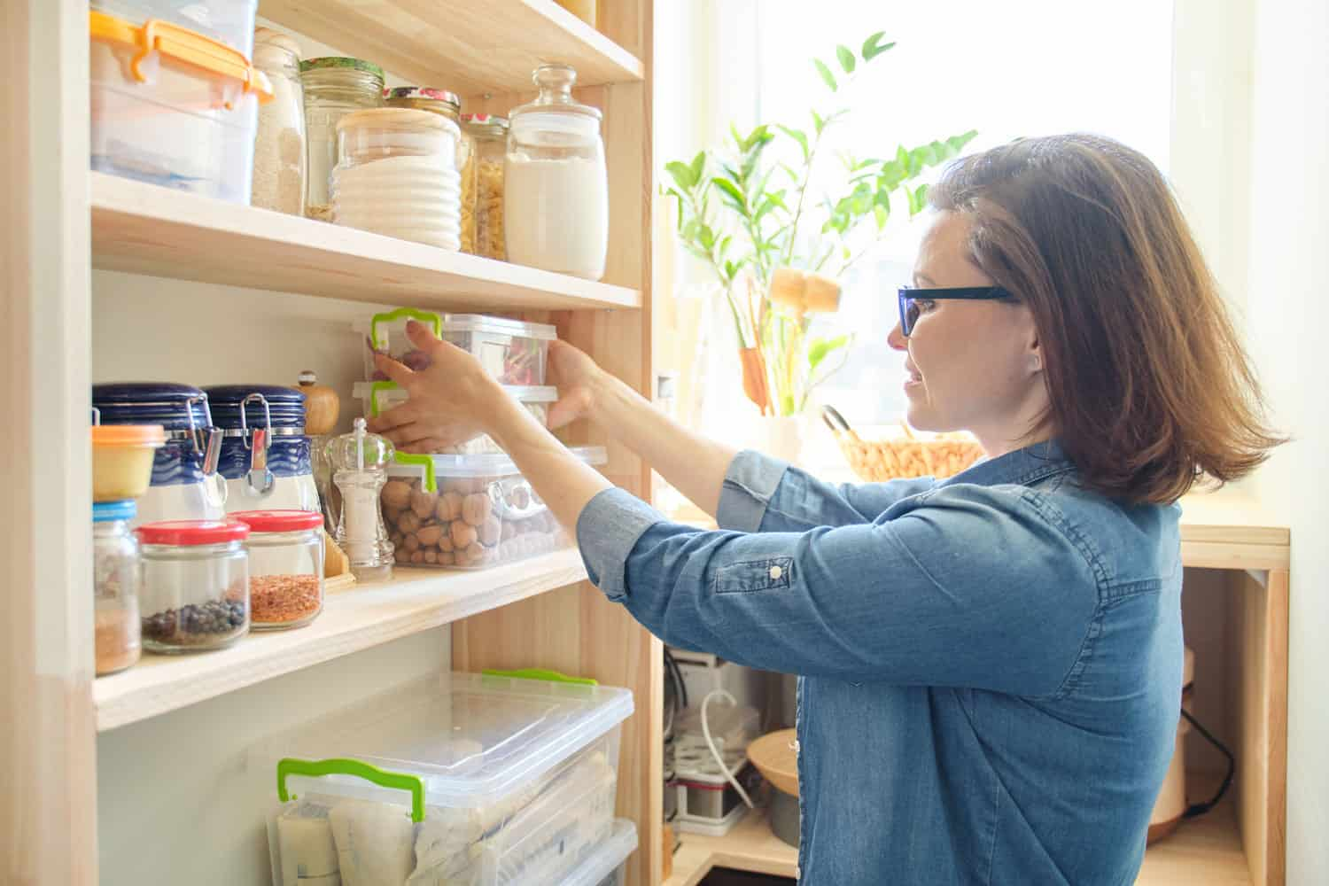 woman getting food container out of pantry