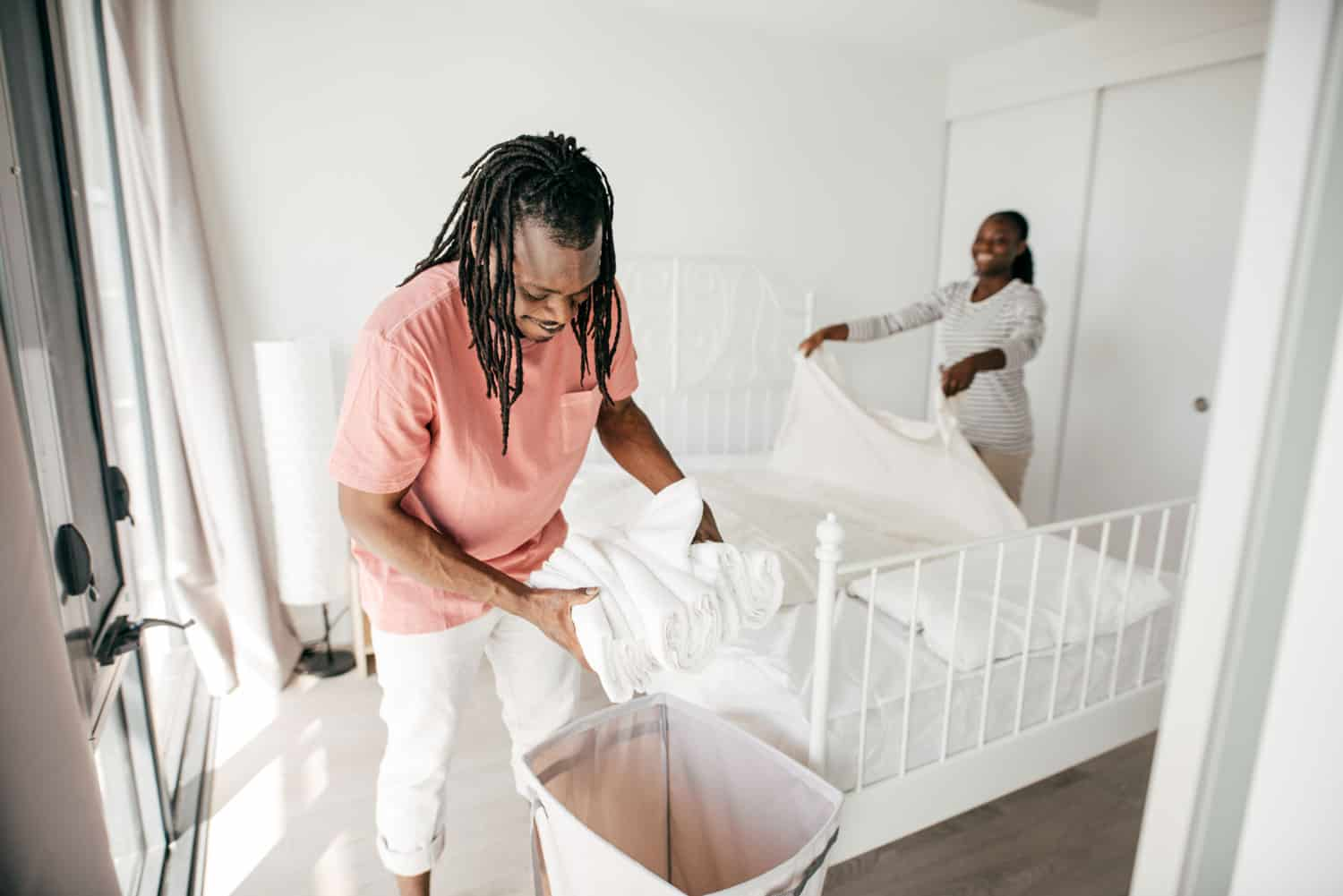 couple folding laundry in bedroom