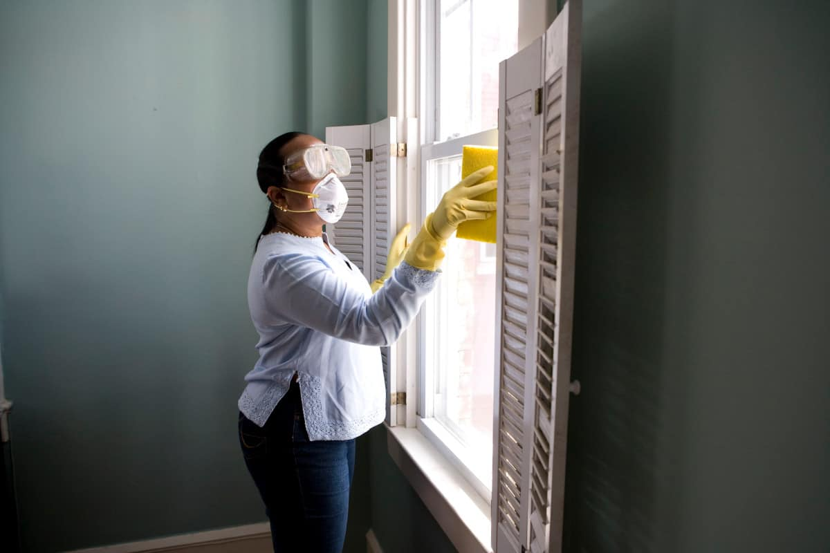 Woman cleaning her windows and blinds