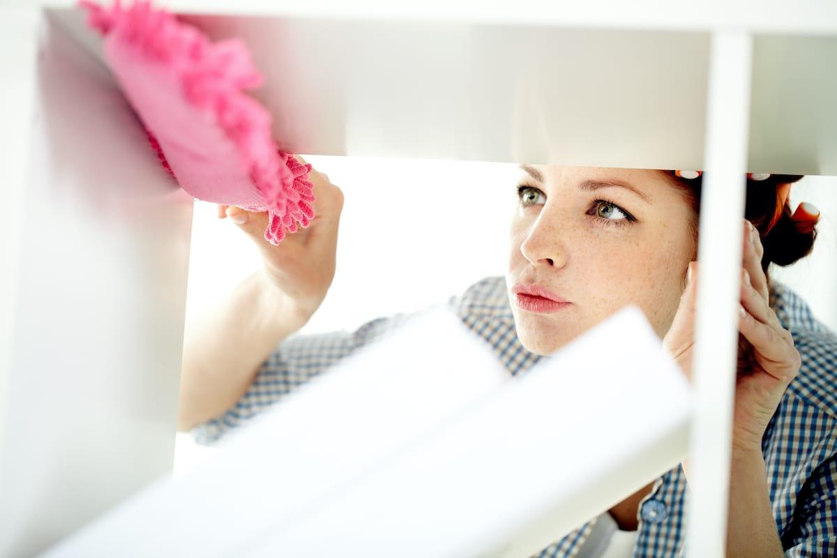 woman dusting corner
