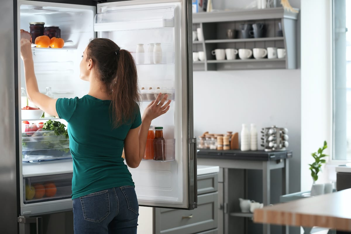 woman getting food out of fridge