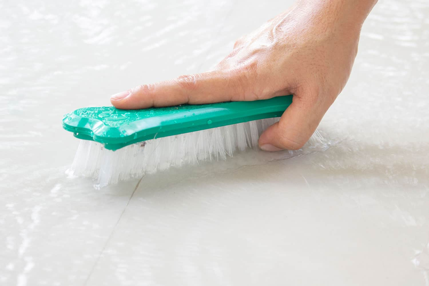 scrubbing grout with brush