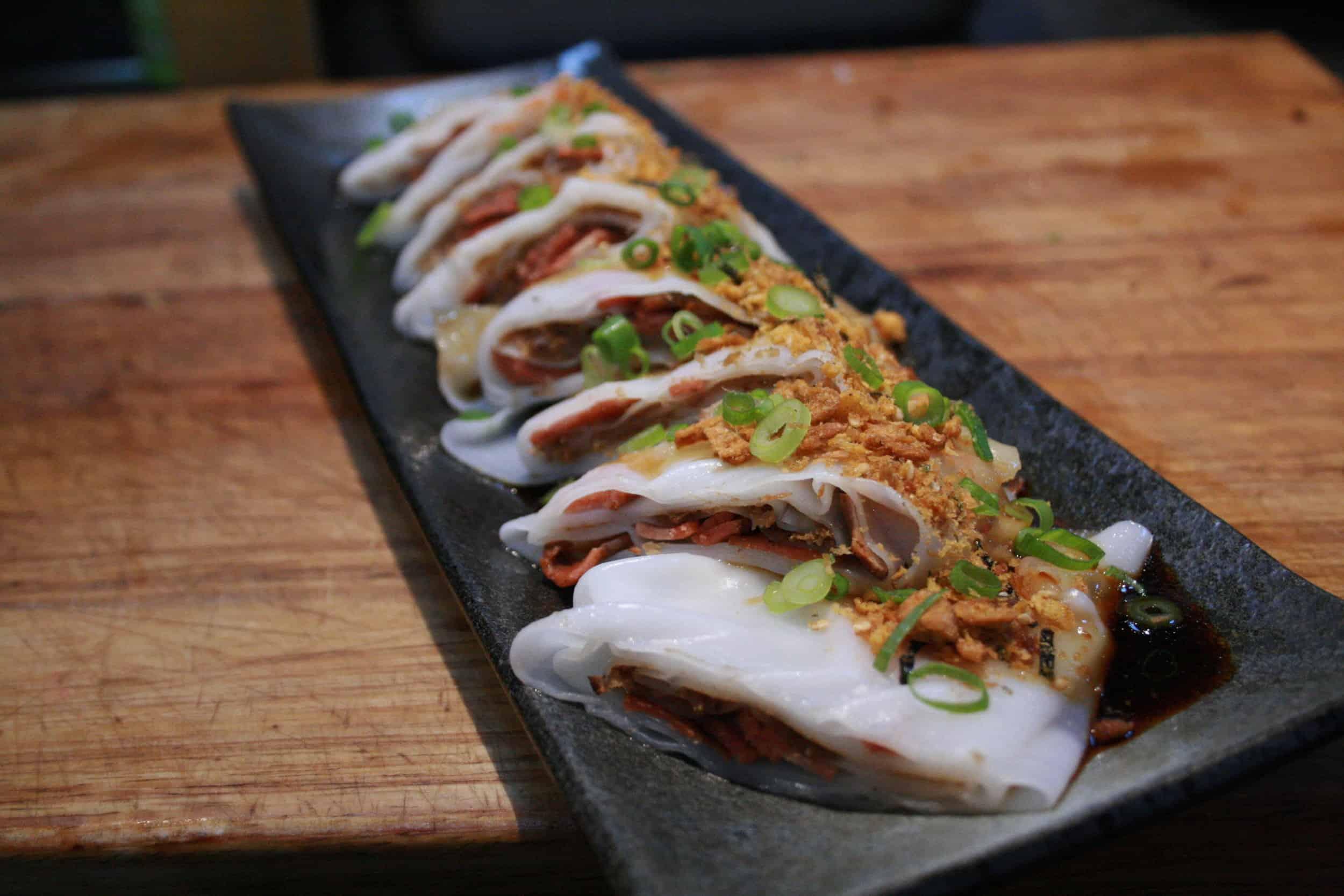 A rectangular plate of vegan dumplings.